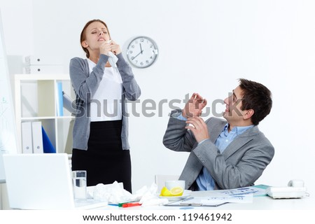 Image of sick businesswoman sneezing while her partner looking at her with anxiety in office - stock photo