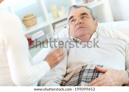Image of sick senior man looking at his wife offering him to take pill - stock photo