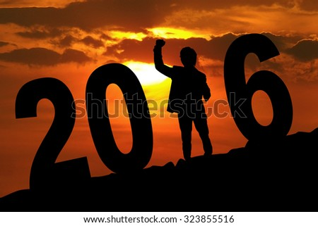 Image of silhouette businessman celebrating new year on the hill with 2016 number. Shot at sunset time - stock photo