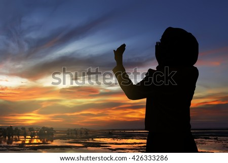 Image of silhouette woman praying with sunset background - stock photo