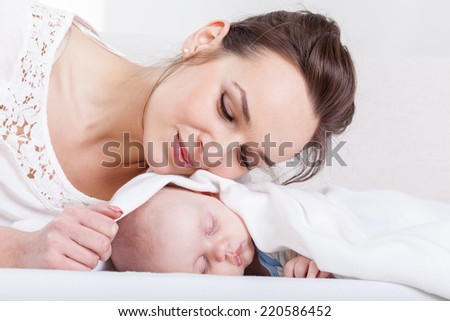 Image of sleeping infant and attractive mum - stock photo