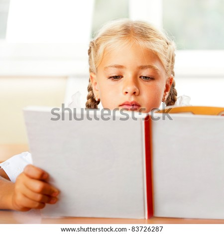 Image of smart child reading interesting book in classroom. Horizontal Shot. She is involved and thinking