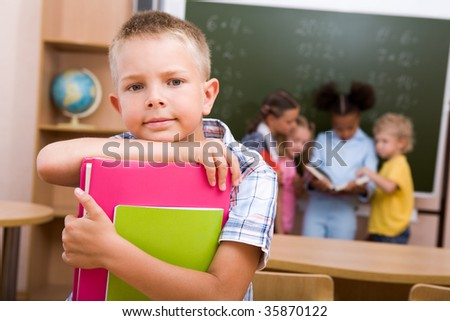 Image of smart lad looking at camera on background of reading classmates - stock photo