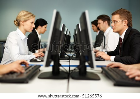 Image of smart people sitting at the tables at computer class - stock photo