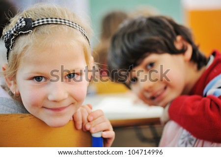 Image of smart schoolboy and schoolgirl sitting at desk and drawing while looking at camera during lesson - stock photo