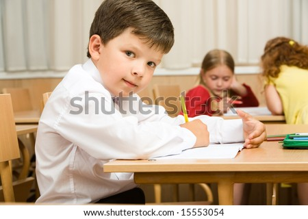 Image of smart schoolboy sitting at desk and drawing while looking at camera during lesson - stock photo