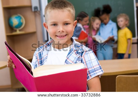 Image of smart schoolboy with open book in hands looking at camera and smiling - stock photo