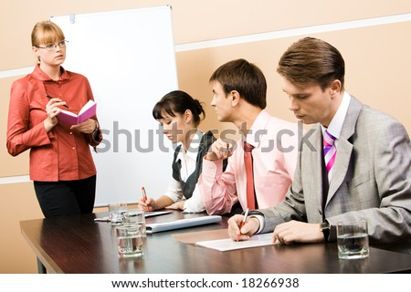 Image of smart teacher looking at businessman and speaking to him in workshop