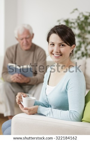 Image of smiling carer and old man reading book - stock photo