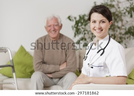 Image of smiling doctor during home visit - stock photo