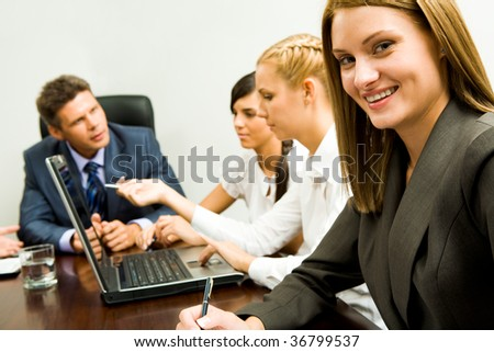 Image of smiling female on background of company of successful partners discussing work - stock photo