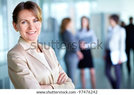 Image of smiling middle aged businesswoman looking at camera