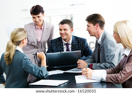 Image of smiling people watching at confident woman while she sharing her idea during meeting