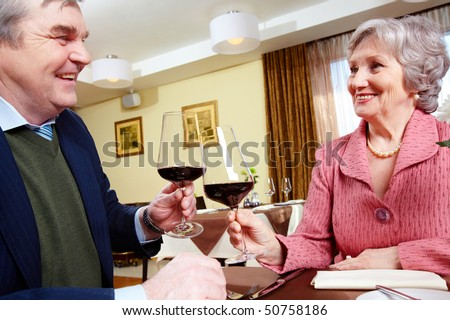 Image of smiling senior couple celebrating their anniversary at a restaurant - stock photo