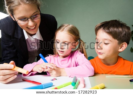 Image of smiling teacher holding highlighter and looking at girlâ??s picture while cute boy expressing his opinion - stock photo