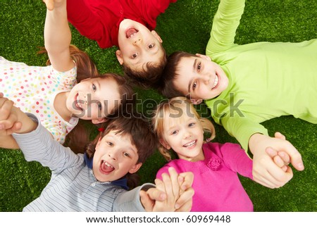 Image of smiling young boys and girls lying on green grass - stock photo