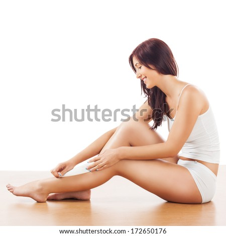 Image of smiling young women, depilating legs. - stock photo