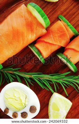 image of smoked salmon slices on dark wood - stock photo