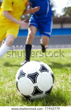 Image of soccer ball in green grass with running footballers on background - stock photo