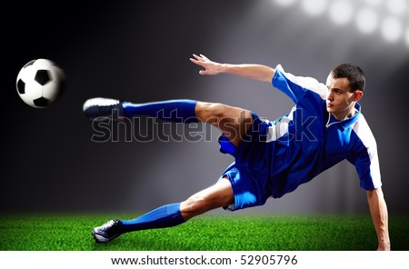 Image of soccer player doing flying kick with ball on football field - stock photo