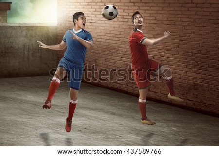 Image of soccer player header on the alley. Street soccer concept - stock photo