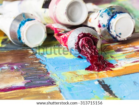 Image of some tubes of oil paints on colorful  painted floor   - stock photo