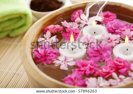 Image of spa therapy, flowers in water, on a bamboo mat. - stock photo