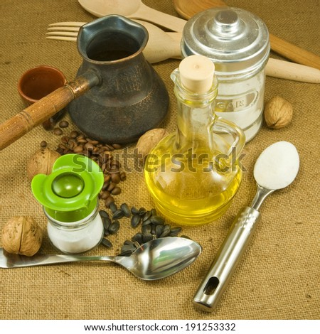 image of spoons, nuts, seeds,butter, salt shaker, coffee beans, a cup on a green background closeup