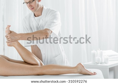 Image of sports masseur during work in massage salon - stock photo