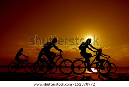 Image of sporty company fife friends on bicycles outdoors against sunset. Silhouette A lot phases of motion of a single cyclist along the shoreline coast Space for inscription - stock photo