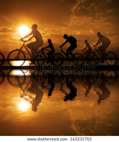 Image of sporty company friends - five people -on bicycles outdoors against yellow sunset background Silhouette A lot phases of motion cyclist along shoreline coast  Space for inscription