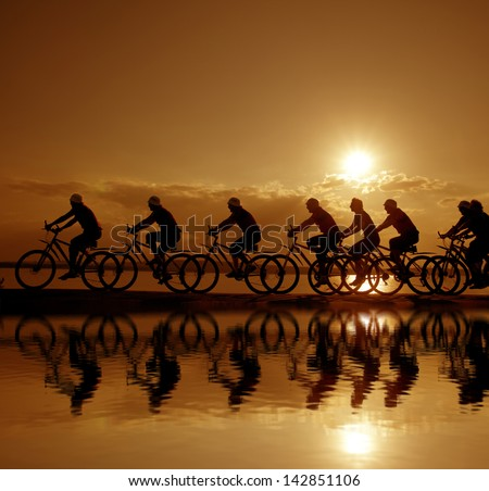Image of sporty company friends on bicycles outdoors against sunset. Silhouette A lot phases of motion of a single cyclist along the shoreline coast Reflection on water Space for iscription - stock photo