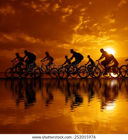 Image of sporty company friends on bicycles outdoors against sunset. Silhouette A lot phases of motion go of ten 10 cyclist along shoreline coast Reflection sun on water Copy Space for inscription - stock photo