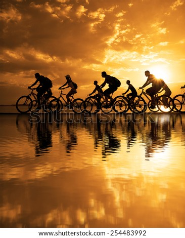 Image of sporty company friends on bicycles outdoors against sunset. Silhouette A lot phases of motion go of nine 9 cyclist along shoreline coast Reflection sun on water Copy Space for inscription