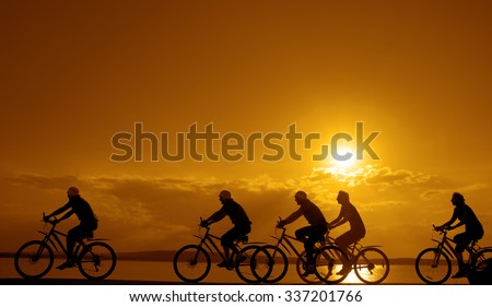 Image of sporty company friends on bicycles outdoors against sunset. Silhouette A lot phases of motion go of five 5 cyclist along shoreline coast Reflection sun on water Copy Space for inscription