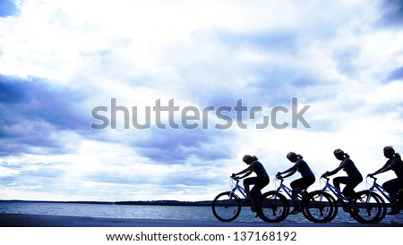 Image of sporty company friends on bicycles outdoors against sunset. Silhouette   The four phases of motion of a single cyclist along the shoreline coast - stock photo