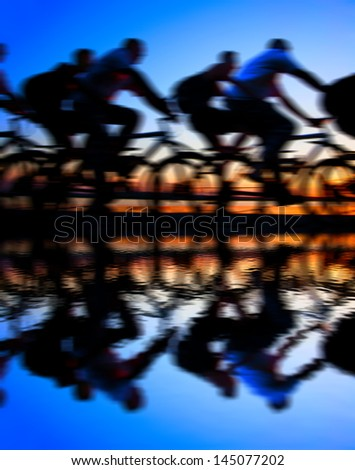 Image of sporty company friends on bicycles outdoors against sunset Silhouette with reflection on water . A lot phases of motion of a single cyclist along the shoreline coast Space for inscription - stock photo