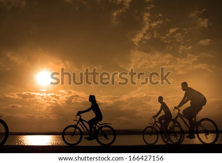 Image of sporty company three friends on bicycles outdoors against sunset. Silhouette motion of 3 cyclist along the shoreline coast and cloudy sunset sky  Space for inscription