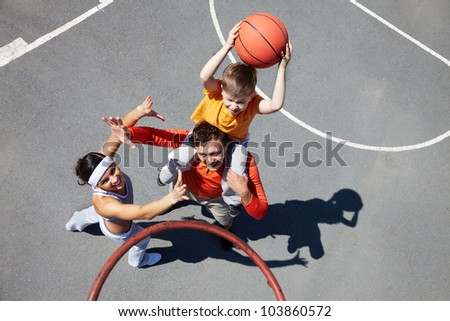 Image of sporty couple and their son playing basketball