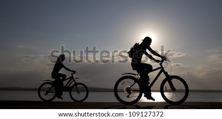 Image of sporty couple on bicycles outdoors against sunset. Silhouette. space for inscriptions - stock photo