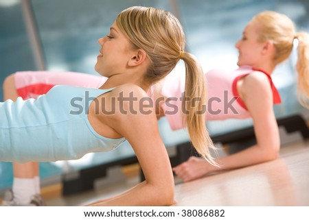 Image of sporty girl doing physical exercise on elbows - stock photo