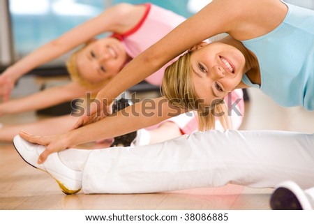 Image of sporty girl sitting on the floor and doing stretching exercise - stock photo