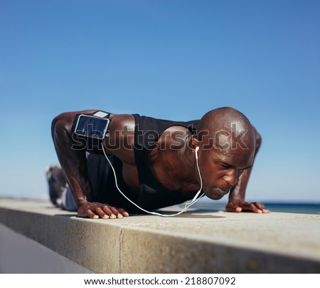 Image of sporty man doing push-ups. Strong young fitness model exercising. African male model workout outdoors. - stock photo