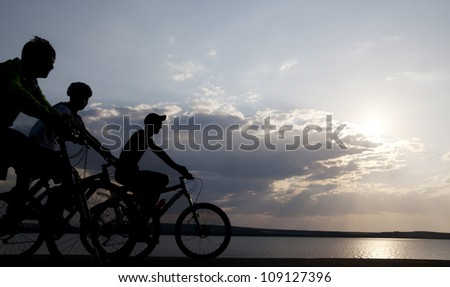 Image of sporty three bicycles outdoors against sunset. Silhouette. space for inscriptions - stock photo