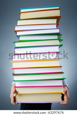 Image of stack of books held by child - stock photo