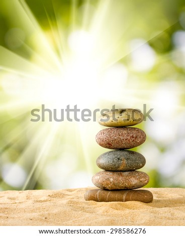 image of stones on sand in the sand against the sun - stock photo