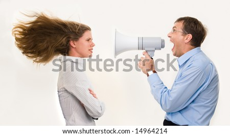 Image of strict boss shouting at businesswoman through loudspeaker so loudly that her hair being blown by strong wind - stock photo