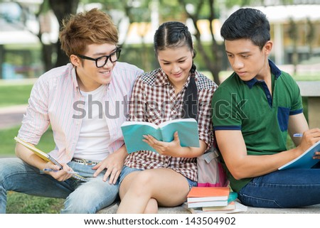 Image of students reading something outdoors together - stock photo