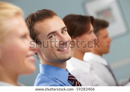Image of successful businessman looking at camera among working partners during conference - stock photo