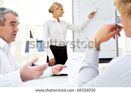 Image of successful businesswoman standing by whiteboard while her colleagues listening to her - stock photo